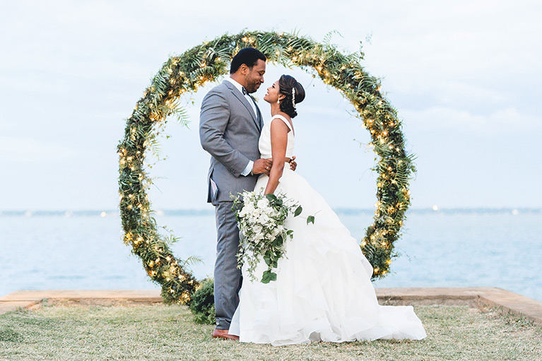 Bride and groom embracing behind a circle of greenery laced with twinkling lights and overlooking the sea