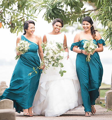Bride walking with two bridesmaids in deep turquoise dresses
