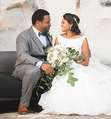 Groom and bride seated on a gray couch with modern artwork behind them