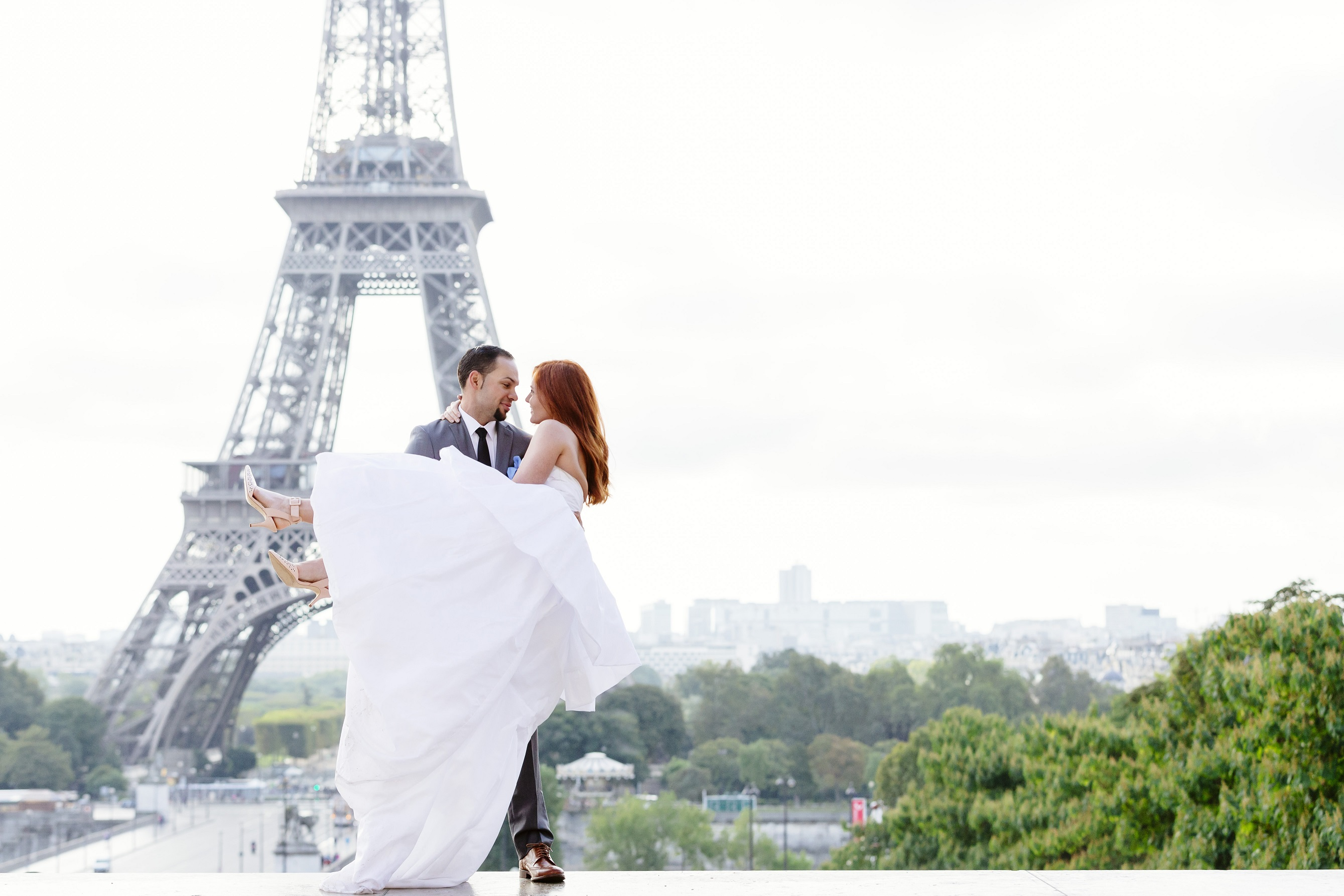 Groom TJ lifts up Bride Emily in front of the Eiffel Tower