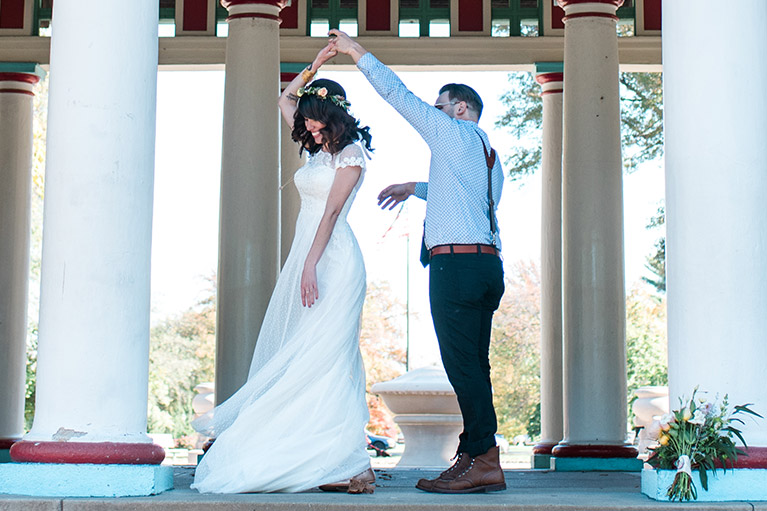 Groom twirling bride in long white dress and flower crown