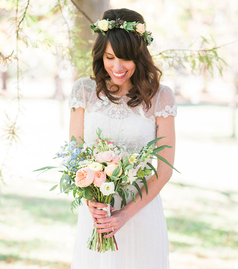 Bride in short sleeve lace wedding dress wearing a flower crown and holding a bouquet of peach flowers.