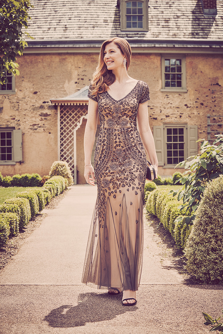Woman in gold cap sleeve special occasion dress with beading