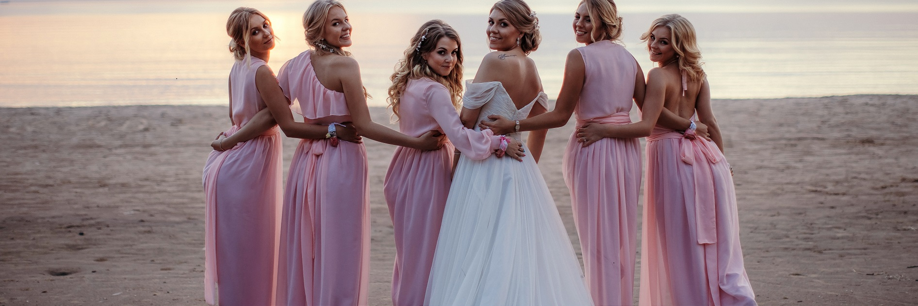 Bride Anna with her bridal party at the beach at sunset.