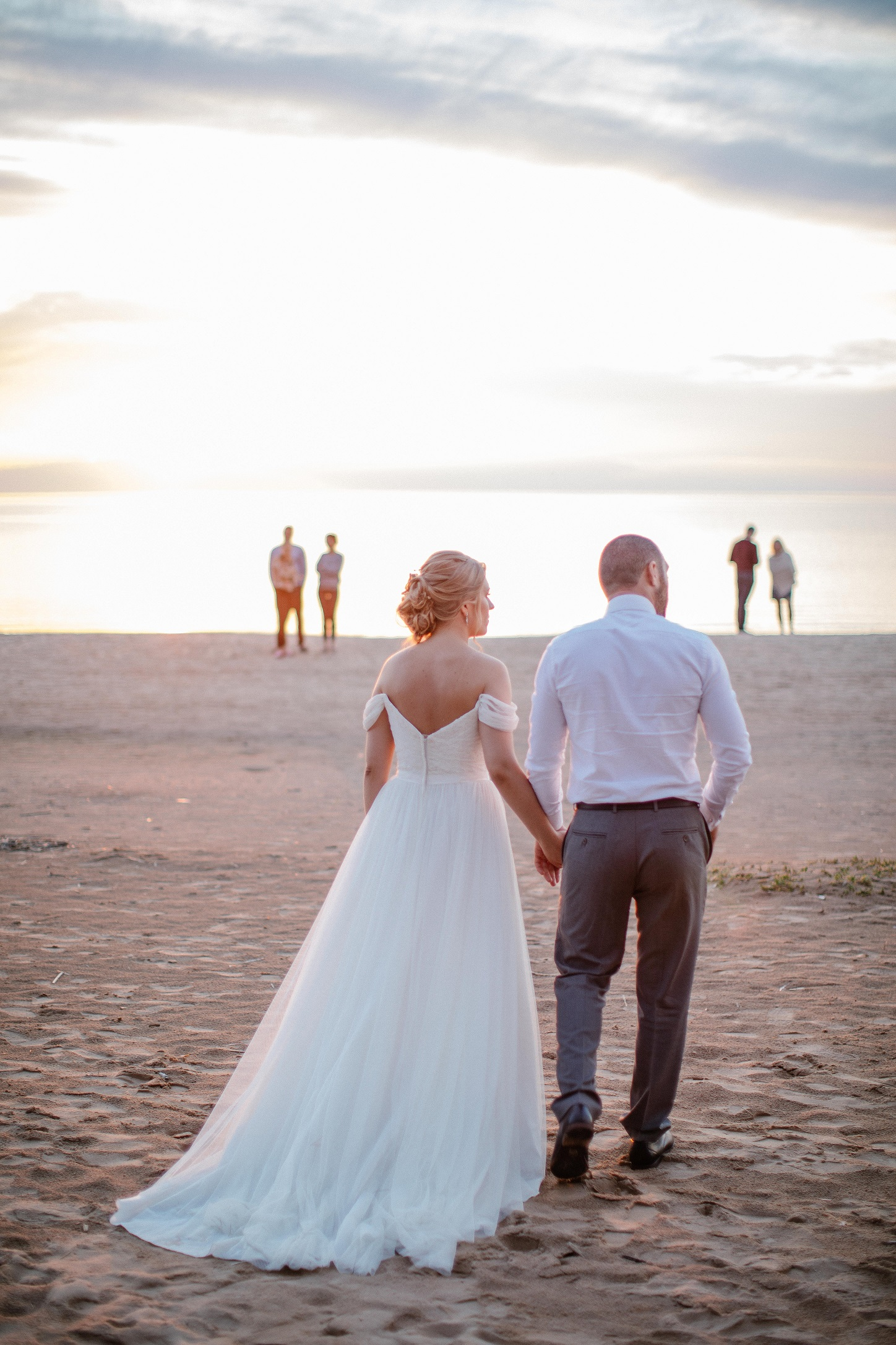 Bride Anna and Groom Levan hold hands on the beach at sunset