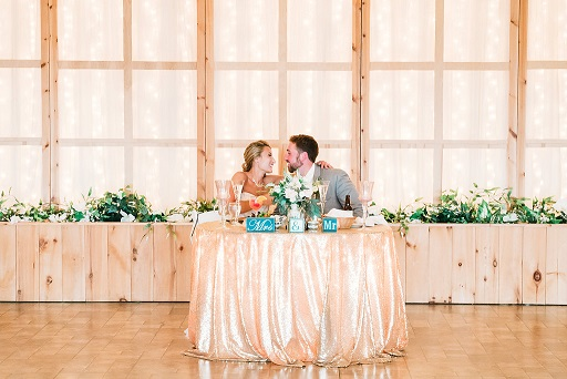 Bride and Groom kiss at reception table