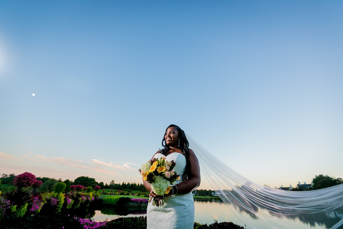 Bride holding a colorful bouquet near a pond with veil blowing in the breeze