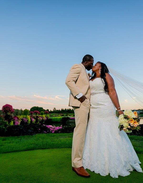 Real bride and groom kiss at sunset