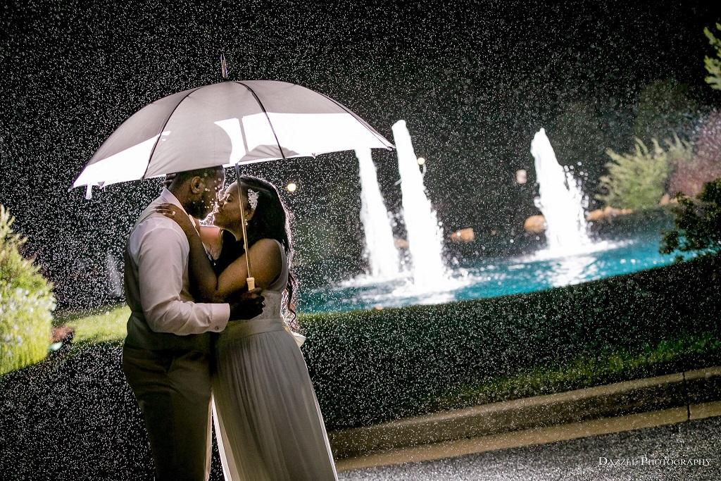Bride and groom dancing under an umbrella in the rain