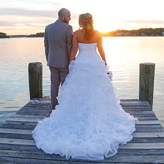 Bride and groom holding hands at sunset on the dock