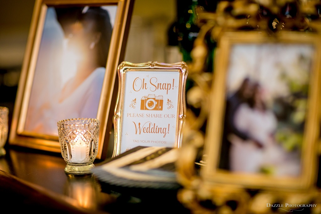 Wedding reception decor featuring family photos and wedding hashtag in vintage gold picture frames