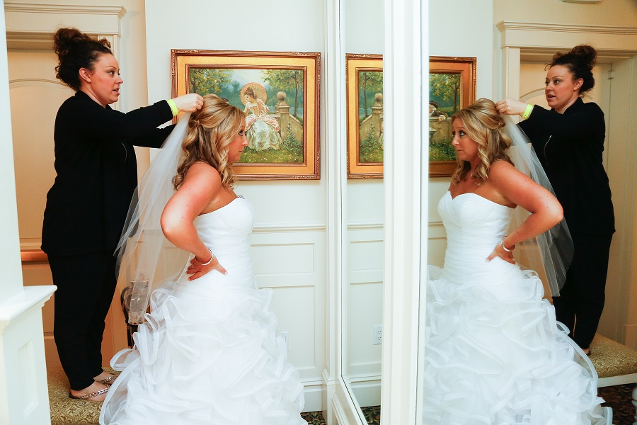 Bride gets ready in the room and puts on veil