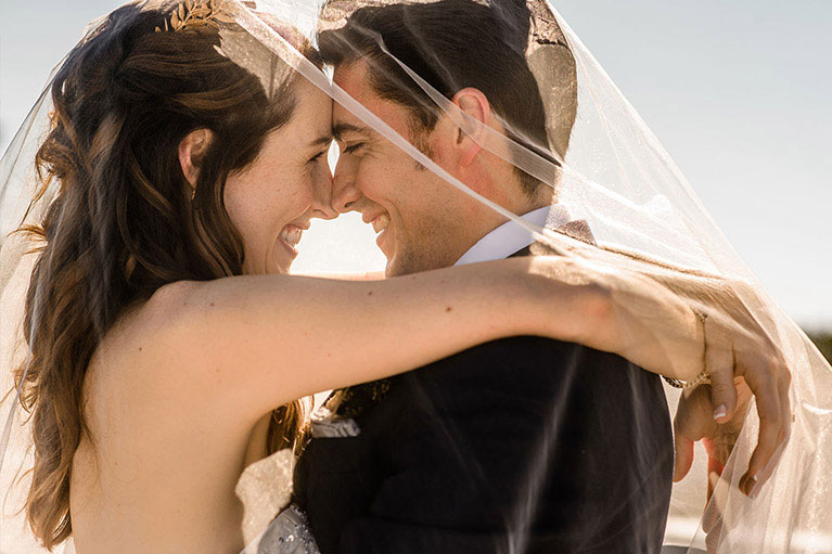 Close up portrait of bride and groom facing each other, foreheads touching underneath veil