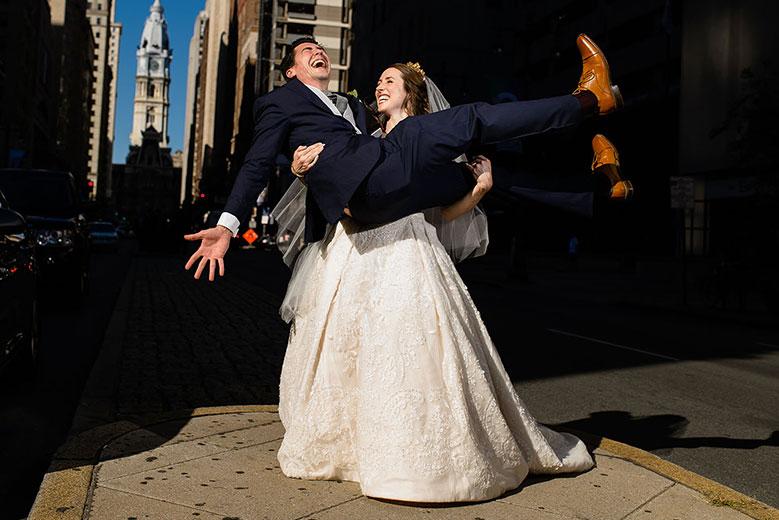 Bride and groom laughing as bride carries groom