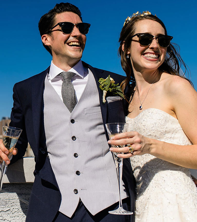 Bride and groom wearing sunglasses and drinking champagne