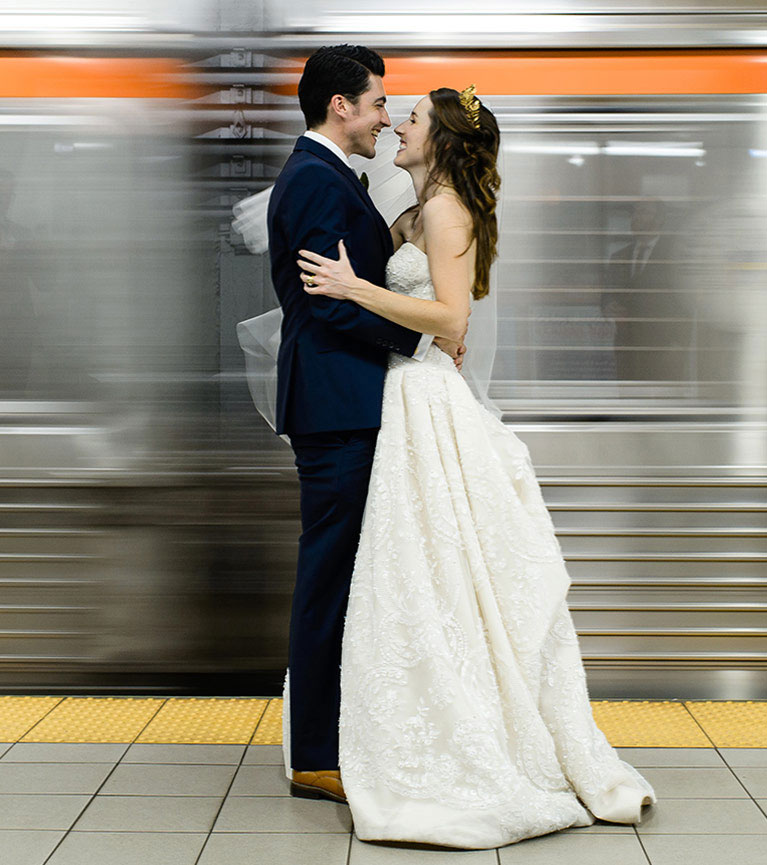 Bride and groom embracing with moving subway car behind them