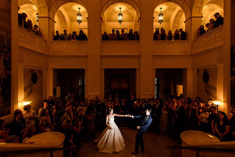 Bride and groom dancing in a dimly lit ballroom