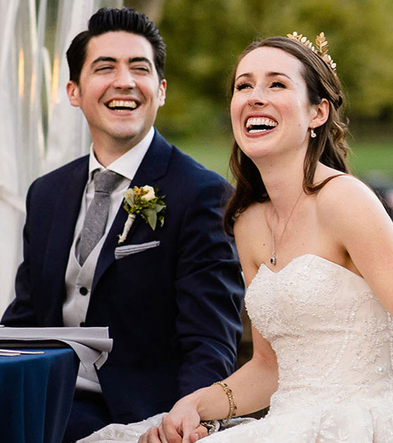Bride and groom laughing while seated at a table during the wedding reception