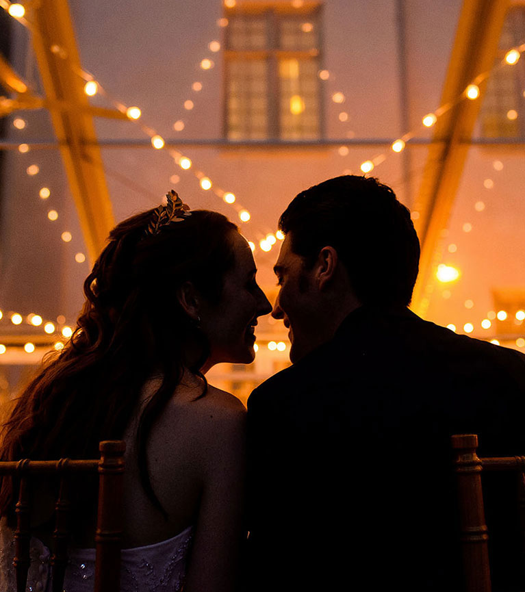 Bride and groom seated and going in for a kiss with twinkling lights behind them