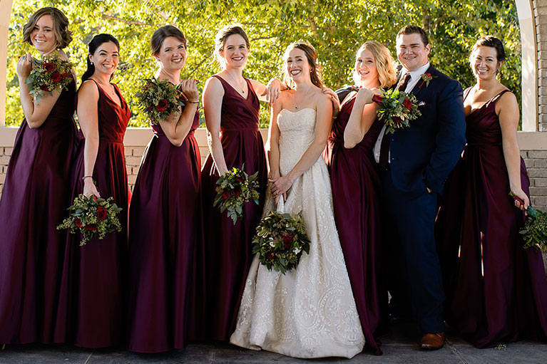 Bride with 6 bridesmaids in wine colored dresses and 1 bridesman in a navy blue suit