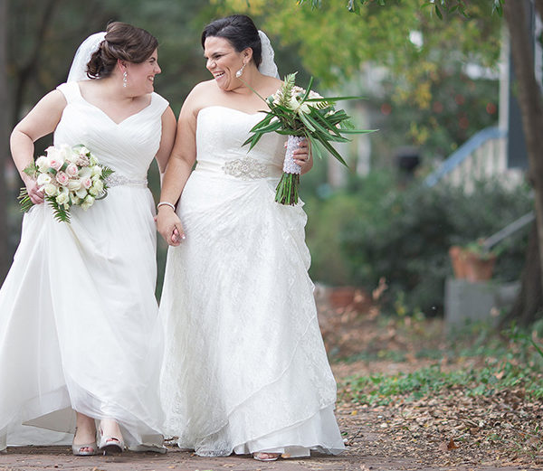 Two brides holding hands and their bridal bouquets while walking through a park
