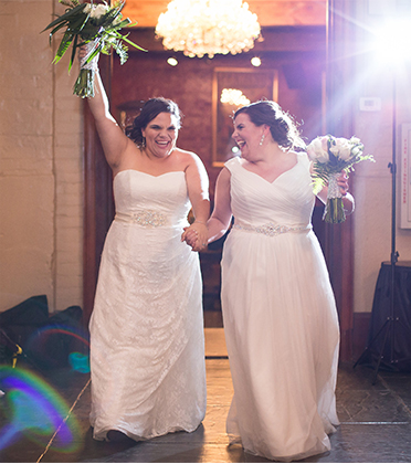 Two brides holding hands as they enter through a door.