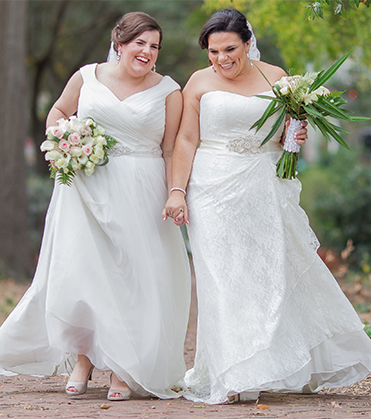 Two brides laughing and holding hands.