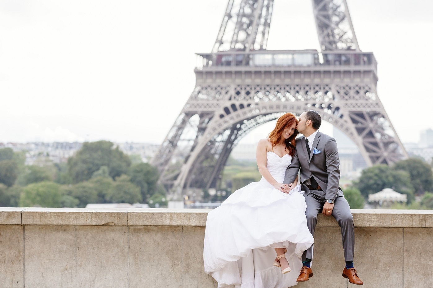 Real Bride Emily and TJ sit in front of the Eiffel Tower.