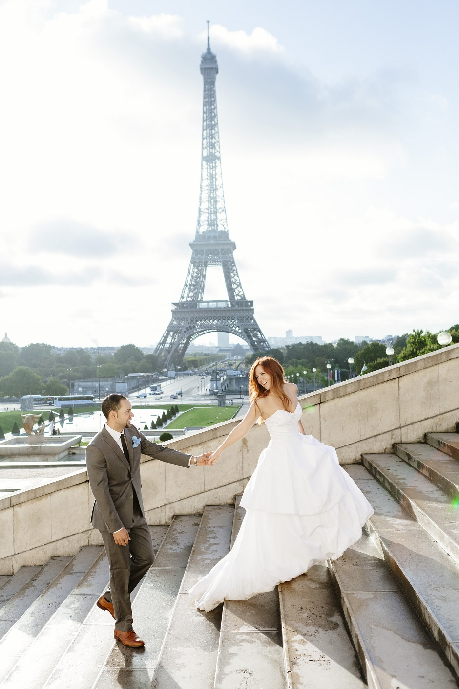Real bride Emily and Groom TJ walk up the steps in front of the Eiffel Tower.