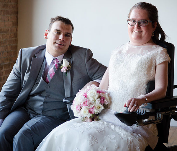 Groom and bride in wedding attire in wheelchairs
