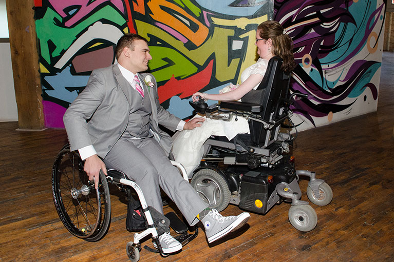 Groom and bride dancing in wheelchairs in front of a wall with graffiti art