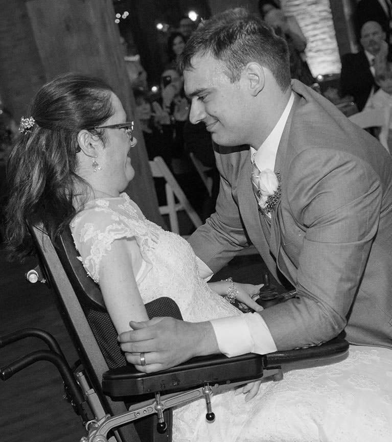 Groom embracing bride in a wheelchair