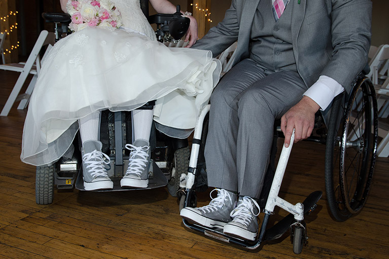 Bride and groom in wheelchairs with matching sneakers