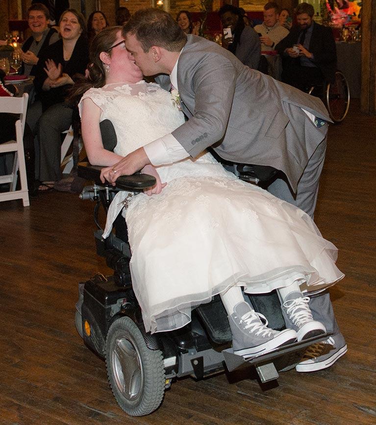 Groom kissing bride in wheelchair