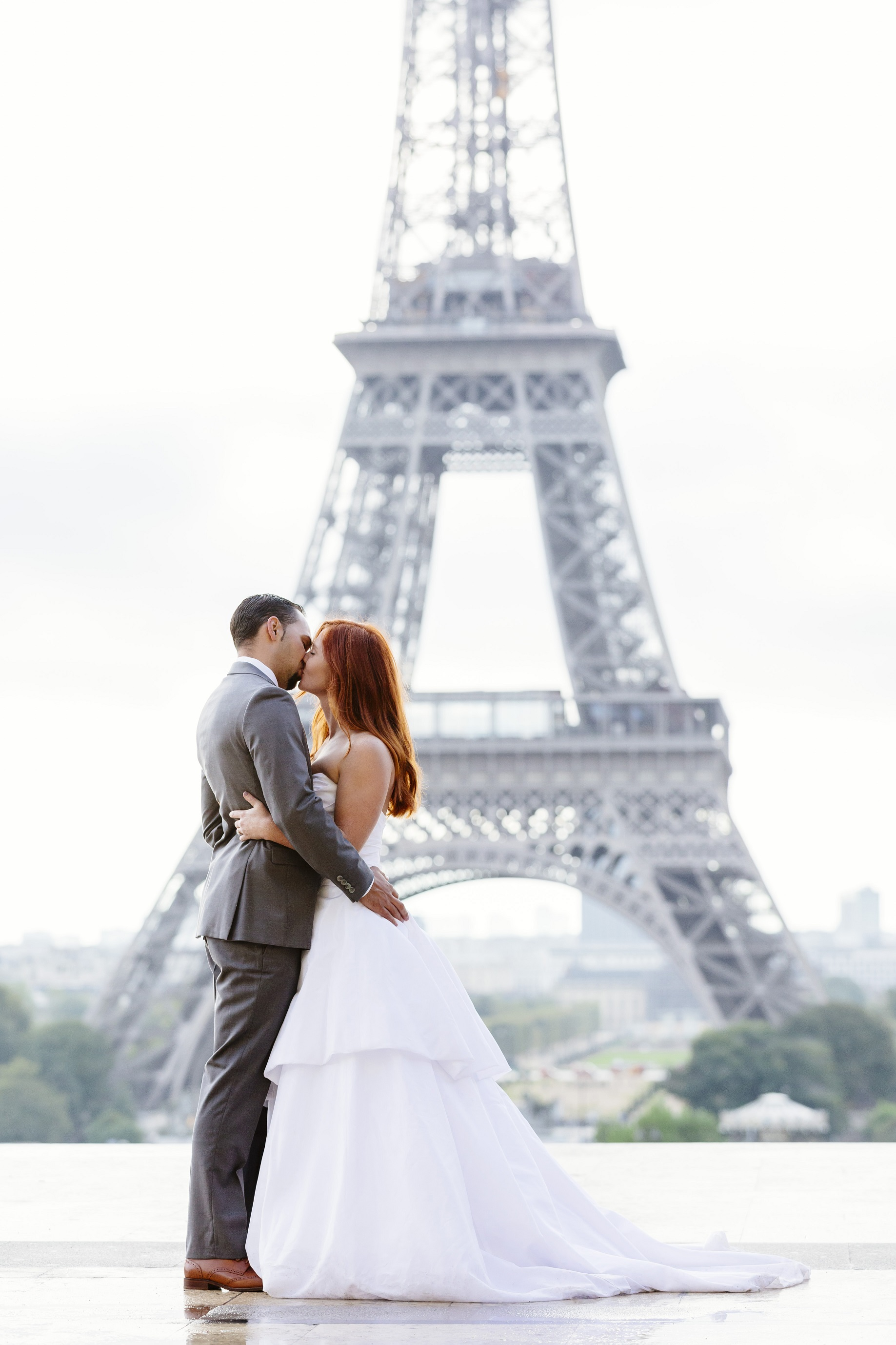 Bride Emily and Groom TJ kiss in front of the Eiffel Tower.