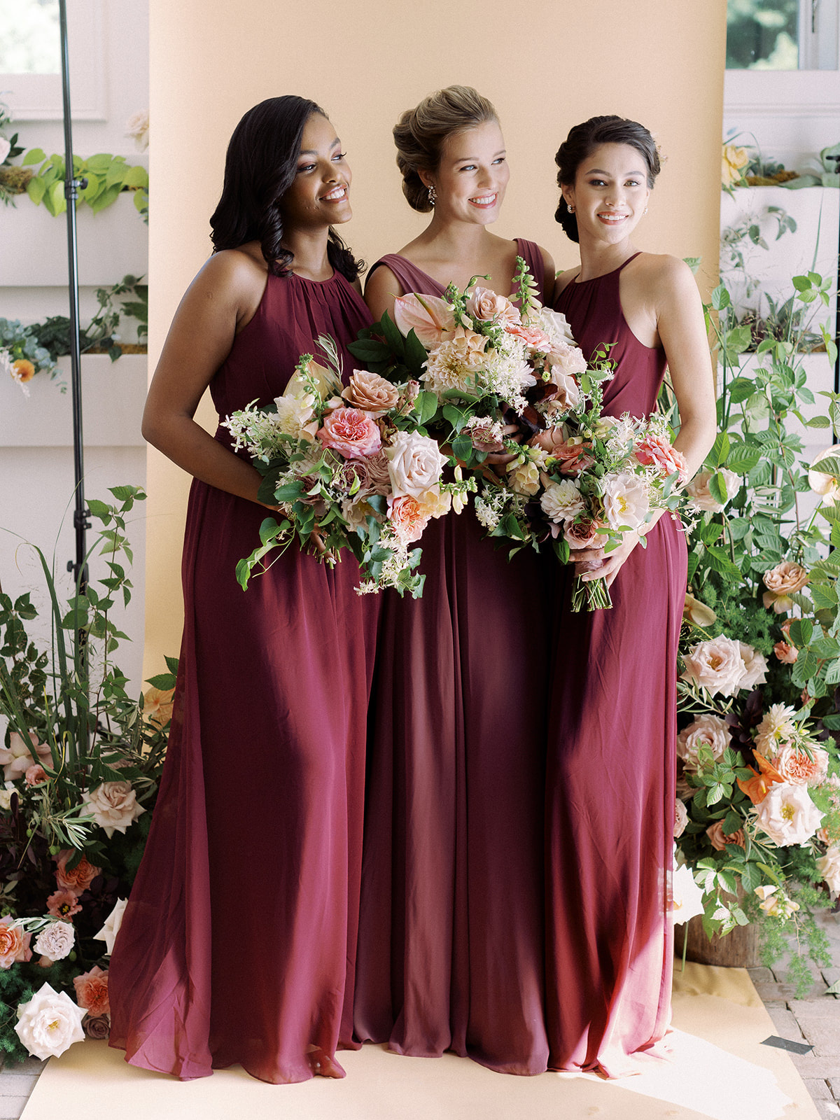 Bridesmaids posing for a group photo wearing David's Bridal gowns in the colors Wine and Chianti for the fall season.