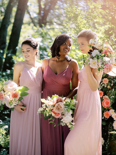 Group of bridesmaids wearing different shades of pink posing for a photo