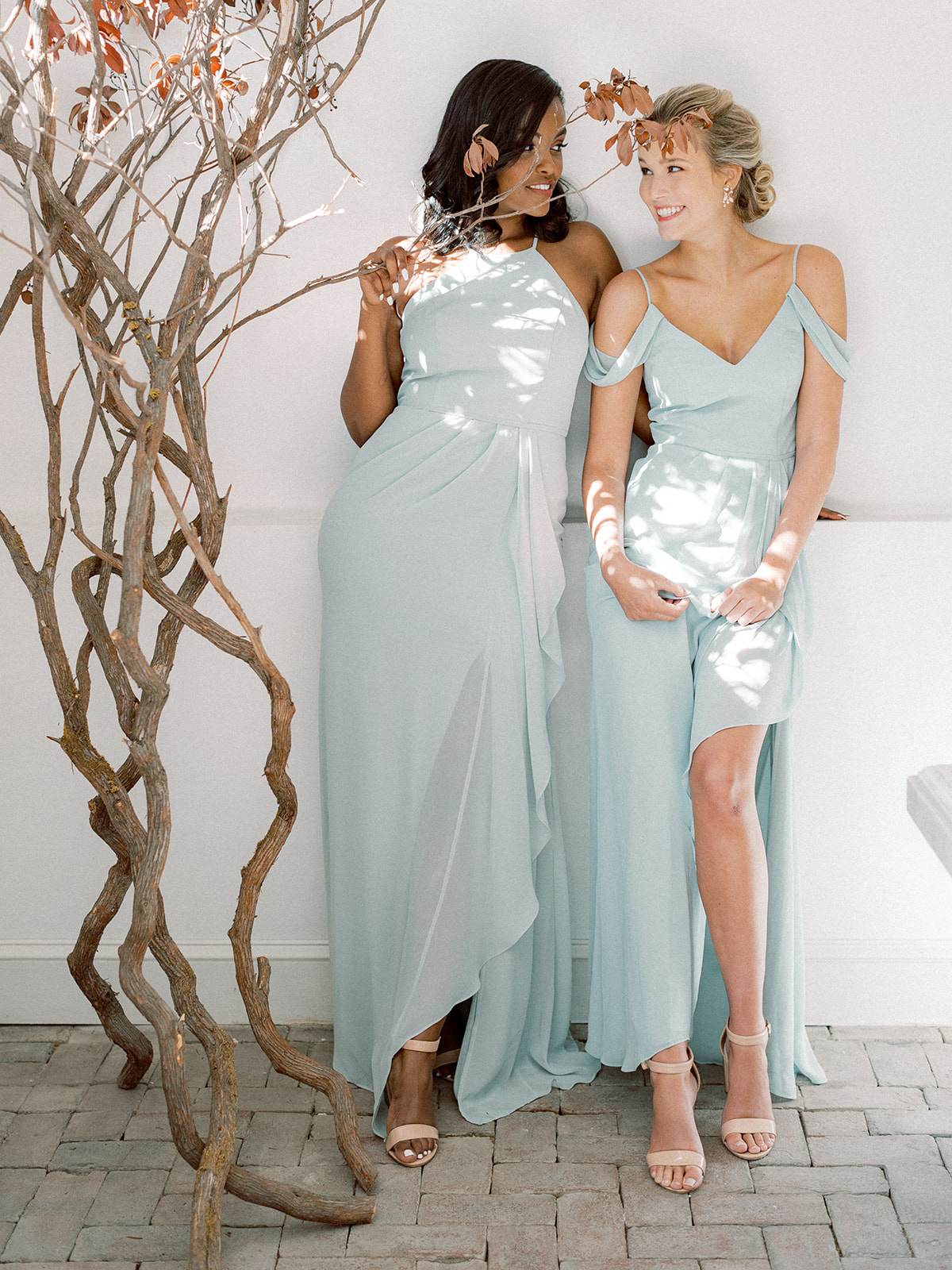 Two bridesmaids wearing dresses in the color Dusty Sage from David's Bridal for the Spring season.