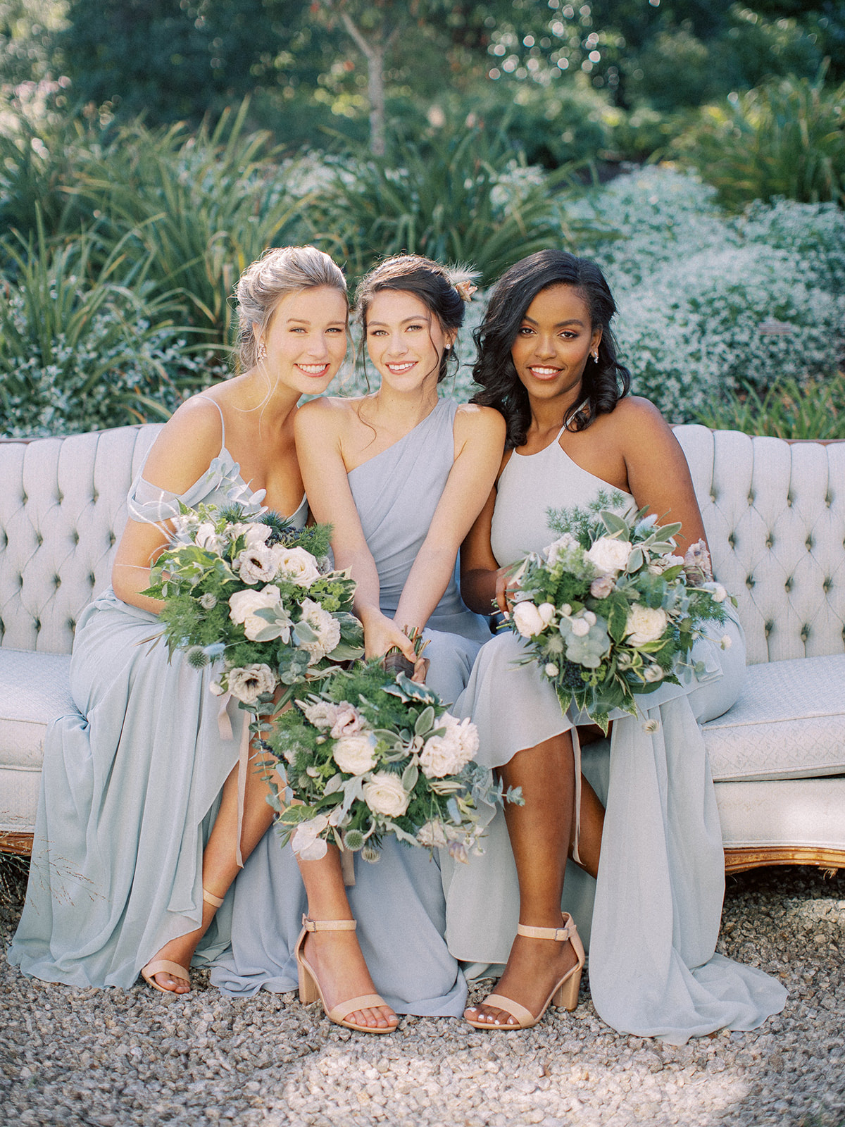 Group of bridesmaids sitting down and posing for a photo wearing dresses in the color Dusty Blue for the Winter season.