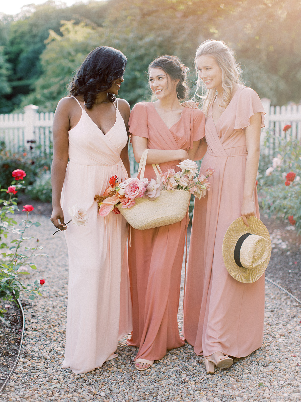Bridesmaids posing for a group photo wearing David's Bridal gowns in the colors Petal, Sedona, and Ballet for the Summer season.