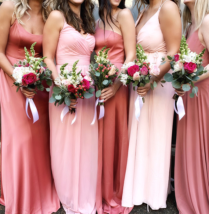 Bridesmaids in coral dresses holding bouquets