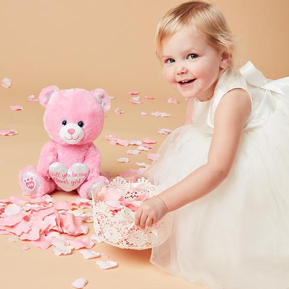 Flower girl holding petal basket with pink Build-A-Bear bear