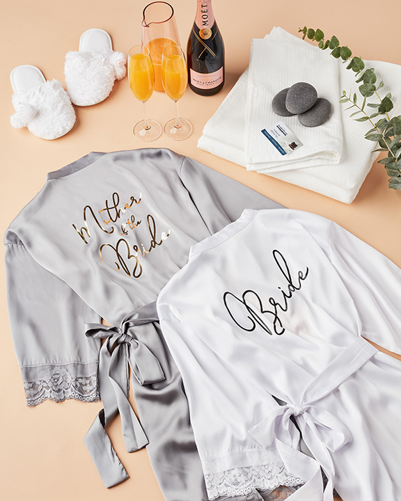 Mother of the bride and bride robe flatlay with mimosas