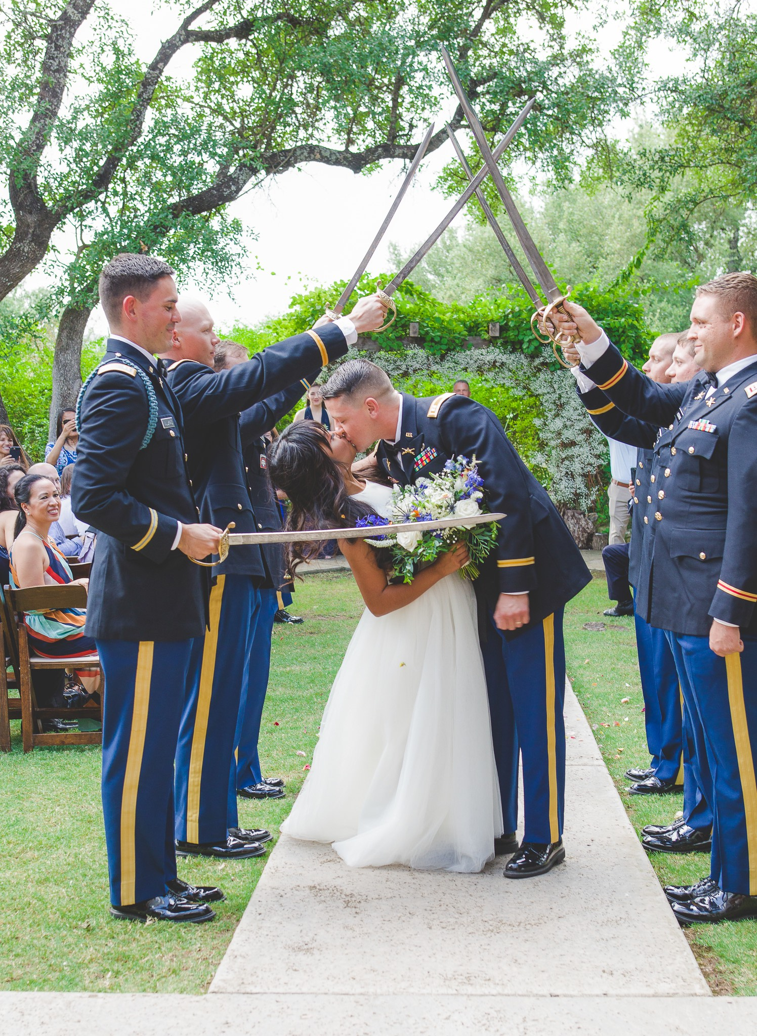 Bride and Groom kissing under military saber arch