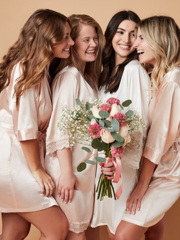 Girls smiling in satin robes holding bouquet