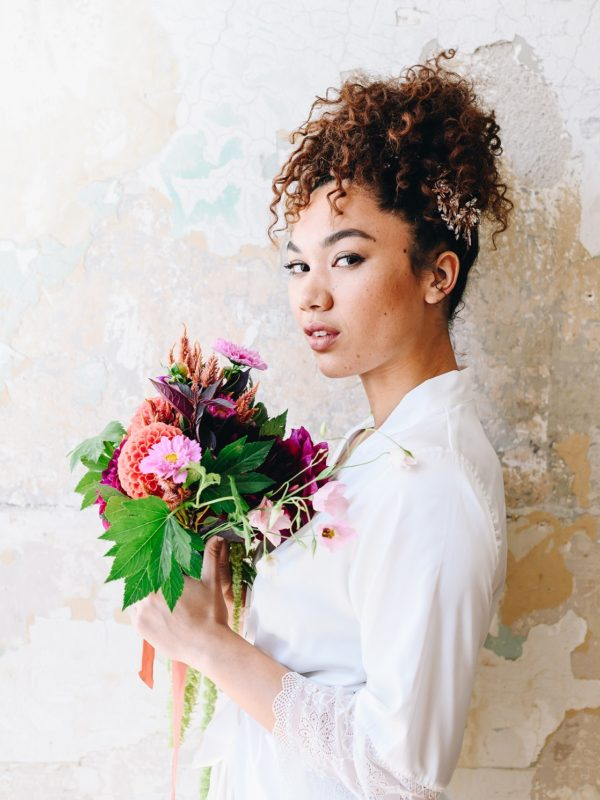Bride holding bouquet with curly wedding hairstyle