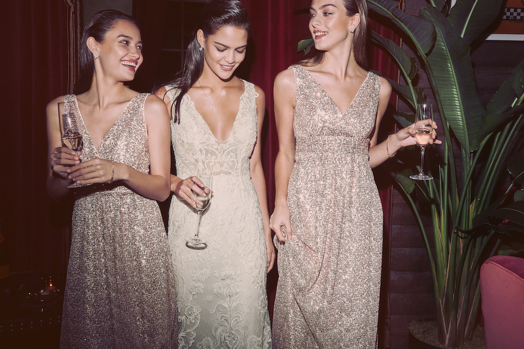 Bride with her two bridesmaids in long gowns in the winter wedding color of gold