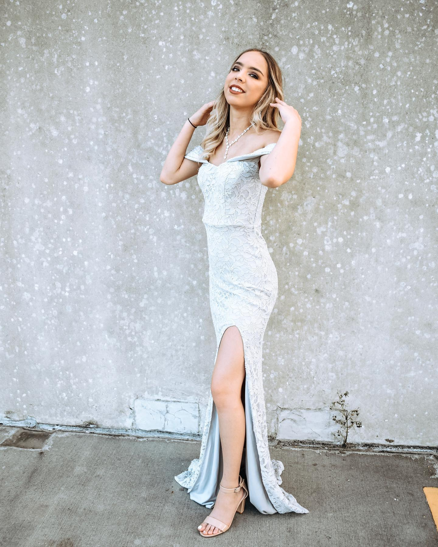 girl in long silver dress with off the shoulder detail and a slit on the side
