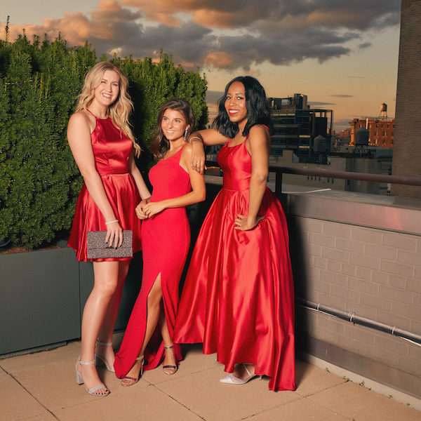 Three young women on a New York City rooftop celebrating the holidays in red David's Bridal dresses.