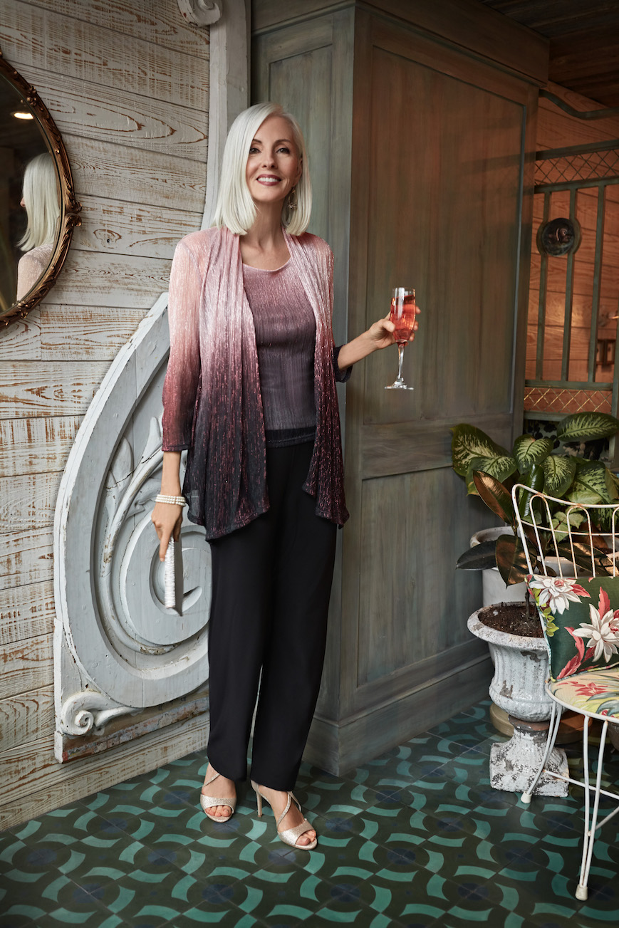 Mother of the bride in an ombre pantsuit holding a wine glass